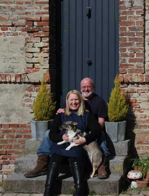 Couple sit posing on a doorstep with their little dog