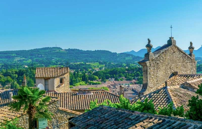View over the roof tops of Vaison-la-Romaine with mountains in the distance under a blue sky