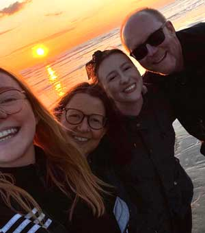 Family pose on a beach at sunset smiling into the camera