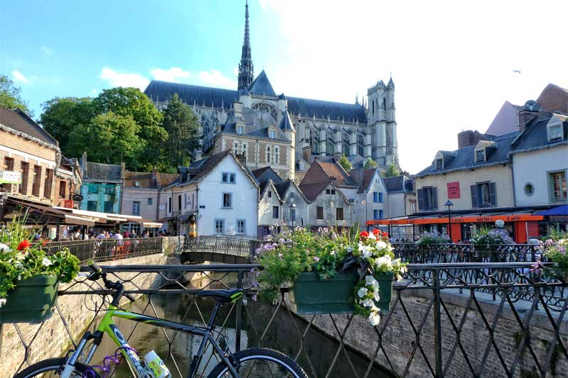 Amiens Cathedral looming over the old district of St Leu, flower filled pots along a cafe lined canal