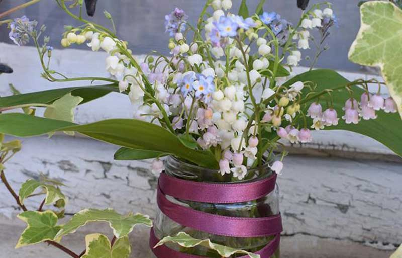 Jam jar filled with Lily of the Valley flowers and wound with pink ribbon