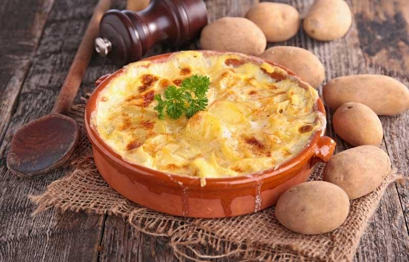 Large crockery dish filled with bubbling potato grattin