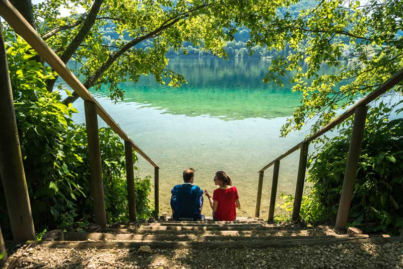 Man and woman sit looking over a crystal clear lake surrounded by forest in Isere, eastern France