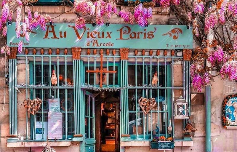 Front of a Paris restaurant with wisteria blooms draped across the door