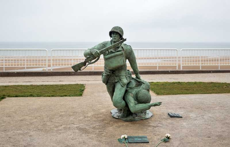 War memorial of two soldiers, one carrying another, Normandy