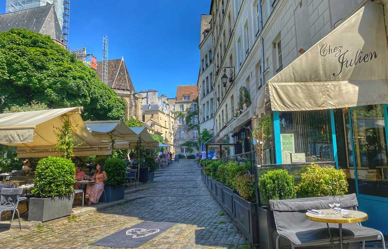 Pretty cobbled road in Paris lined with cafes and restaurants