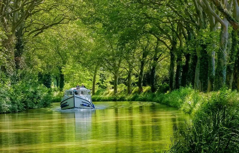 Boat floats gently on the Canal du Midi under a canopy of trees