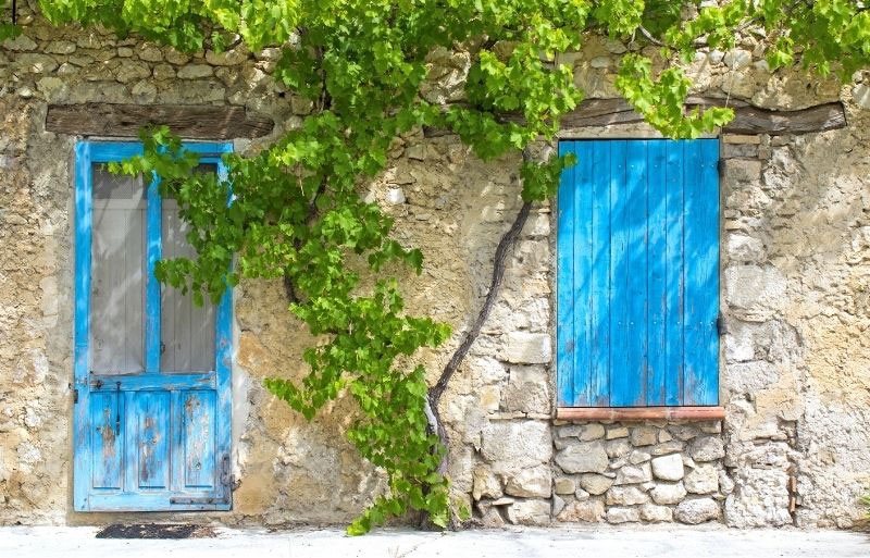 Blue door and blue shutters on stone house, typical French property
