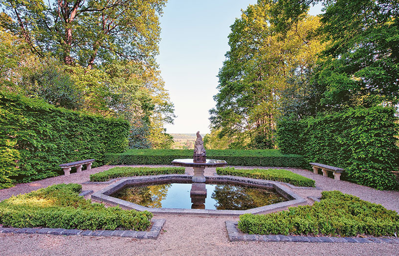 View across a formal parterre garden with pond to countryside in Yvelines, France