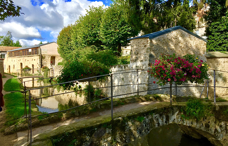 Old stone bridge over a narrow river in the village of Chevreuse, Ile de France