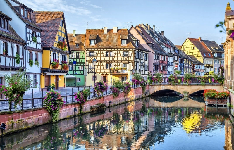 Bridge over river in Colmar flowers in baskets all along the river