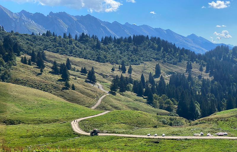 A tractor drives along a narrow alpine road with a backdrop of mountains