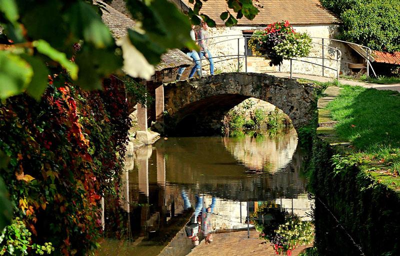 People cross a bridge in the village of Chevreuse