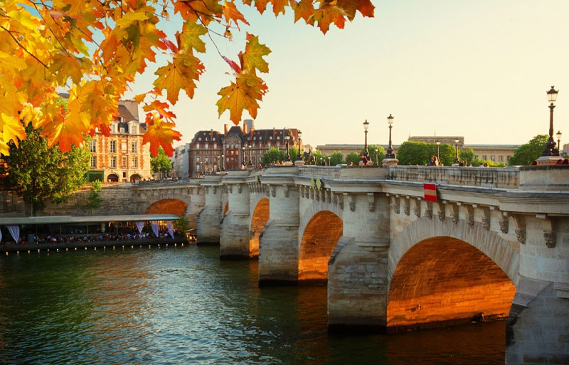 Sunset over Pont Neuf in Paris in autumn turning leaves of trees gold