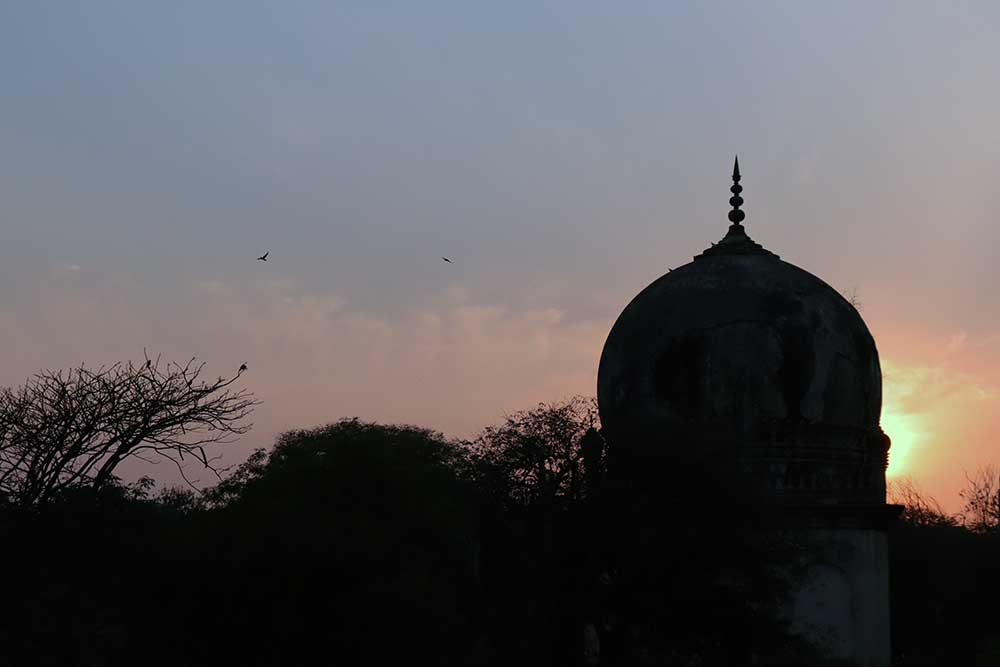 sunset behind premamati's tomb, qutb shahi tombs, hyderabad, india