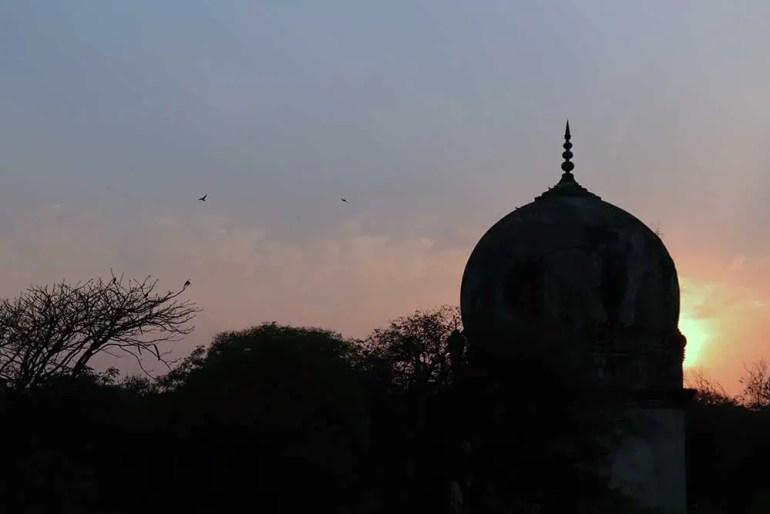 sunset behind premamati's tomb, qutb shahi tombs, hyderabad, india