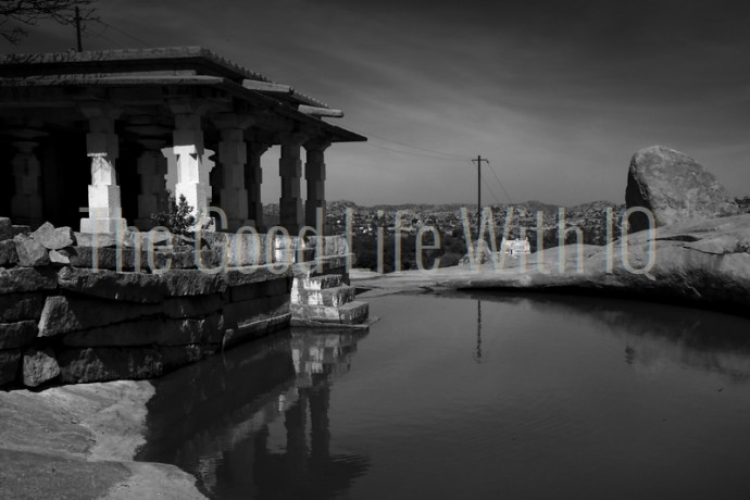 A stone temple next to a pond on Hemakuta Hill in Hampi, India