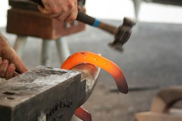 Blacksmith working a lucky horseshoe