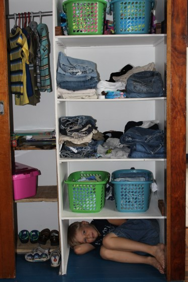 Matt worked hard to organized the three E's clothes and toys into a functional system. Elijah tried Ezekiel's wardrobe space on for size.