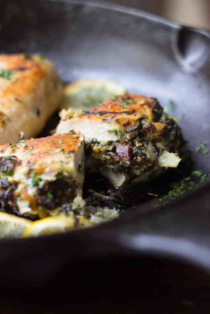 Side shot of spinach artichoke stuffed chicken in a skillet