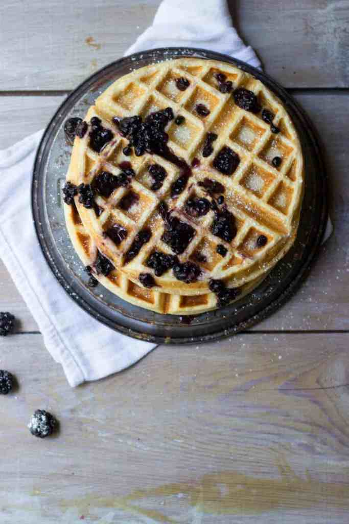Overhead shot of lemon meringue waffles with blackberry maple syrup stacked.