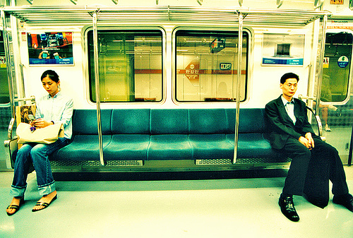 korean-man-and-woman-sitting-apart-on-subway