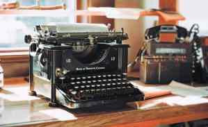 classic black typewriter on brown wooden desk