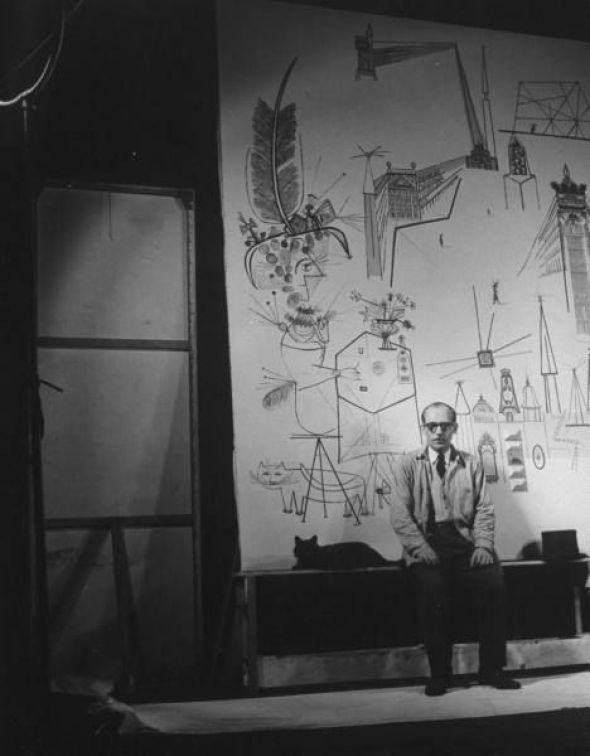 Artist Saul Steinberg w. Gjon Mili's cat Blackie in front of mural he is painting
