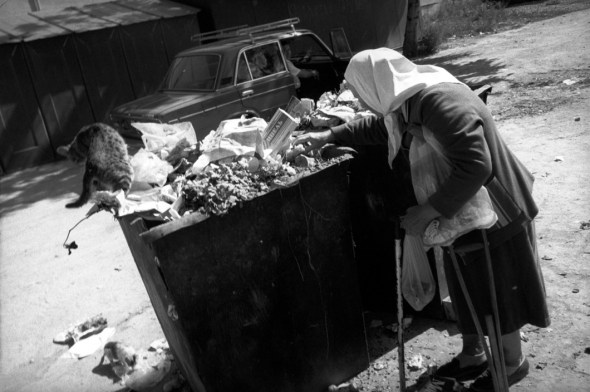 Josef Koudelka, UKRAINE. Odessa. 1993. An old woman and cat sort through a city trash can.