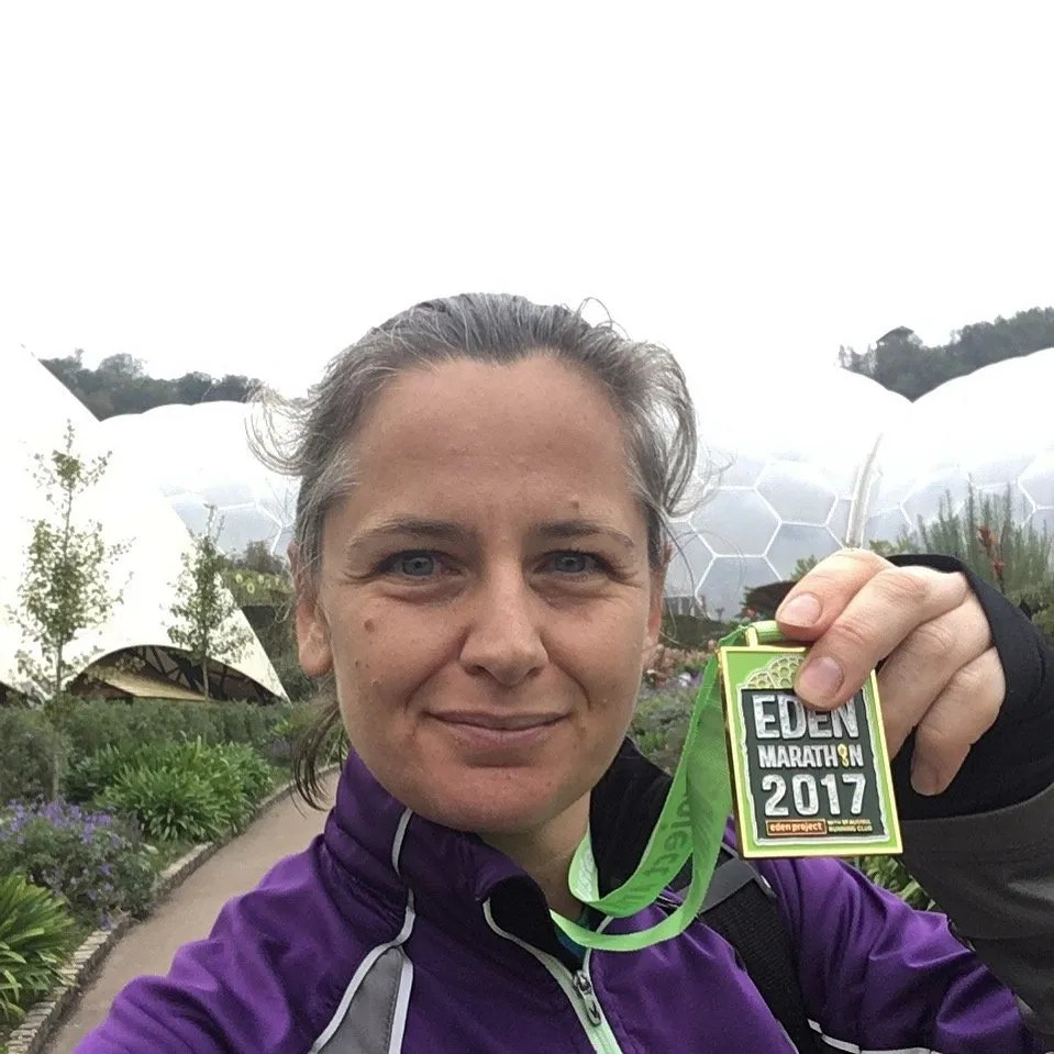 The Eden Marathon Woman Holding medal