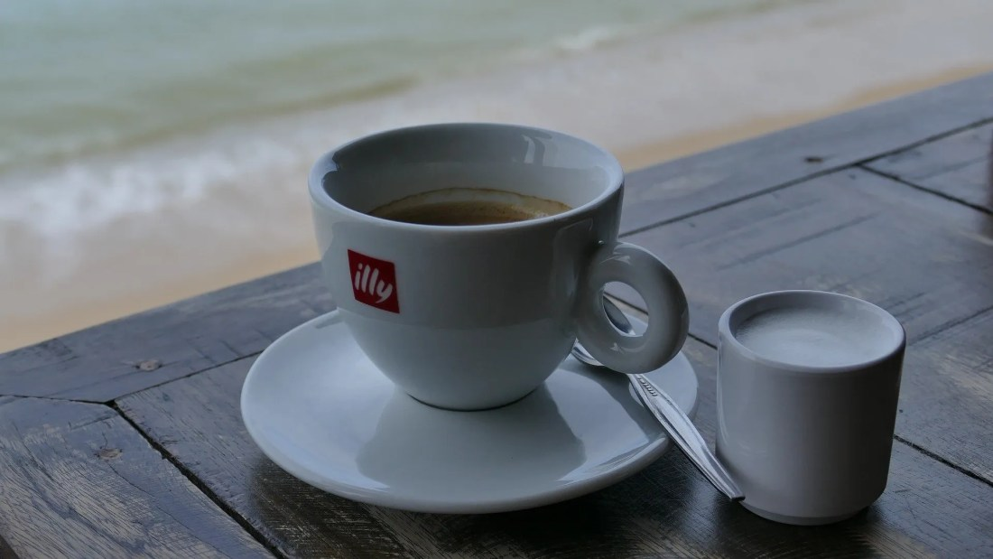 Cup of coffee and milk by the sea