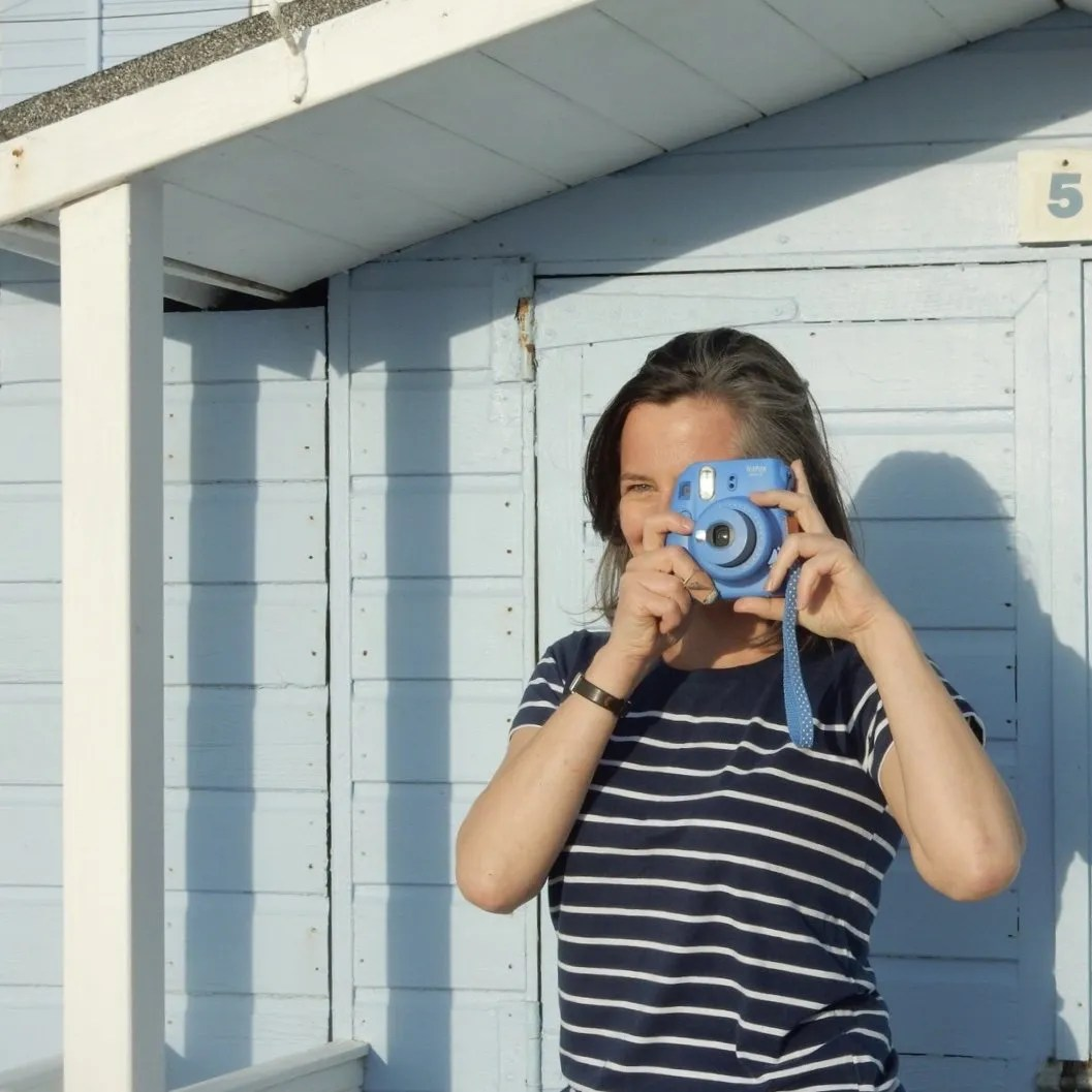 Lady with Instax Camera In Front Of Beach Hut