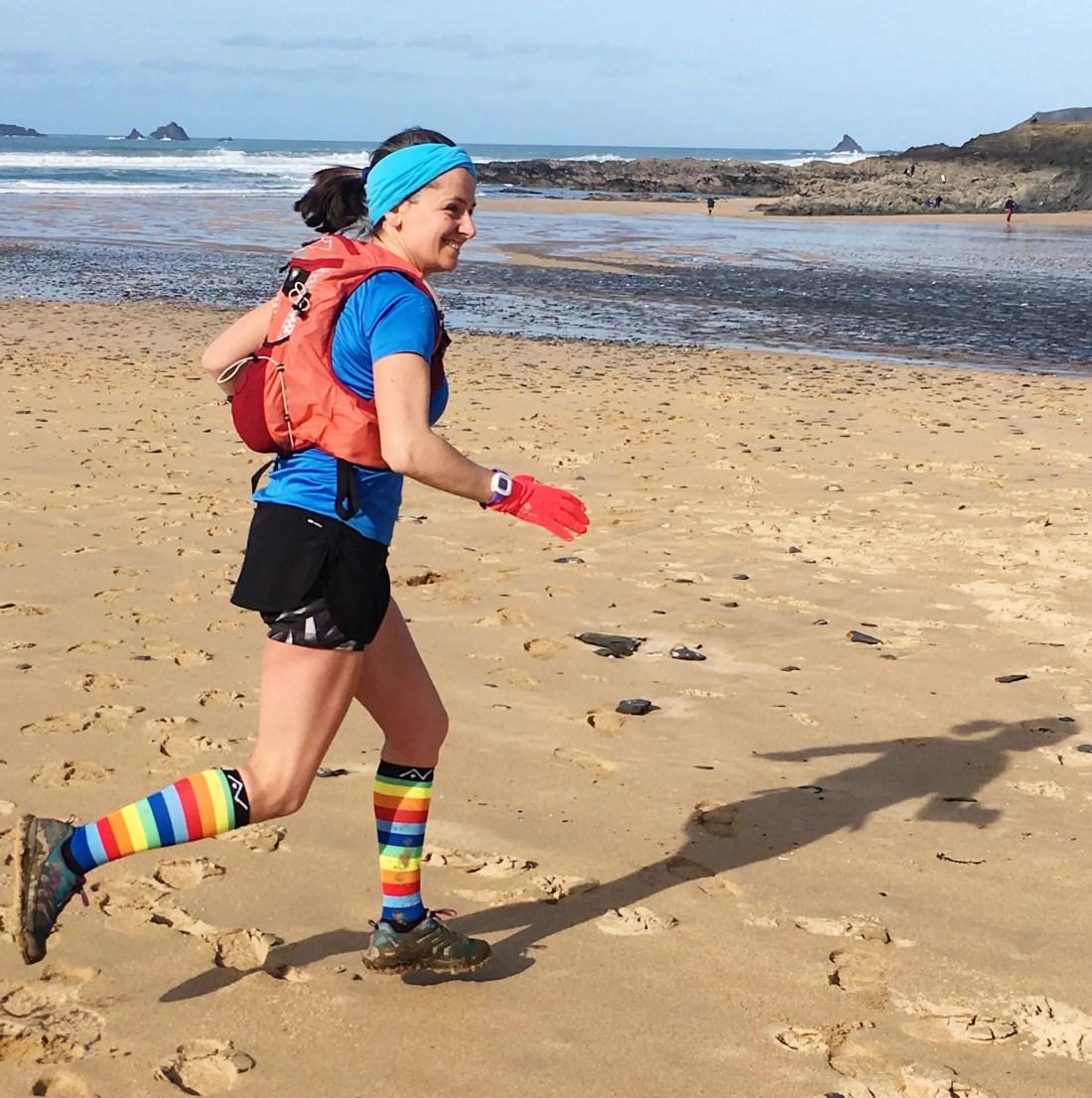 Woman running beach cornwall