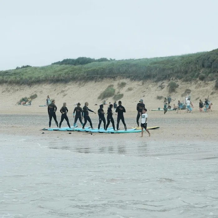 People having a surfing lesson Fistral Beach