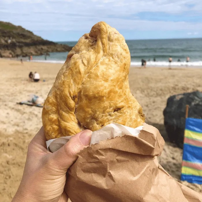A cornish pasty with Porthgwidden beach in the background