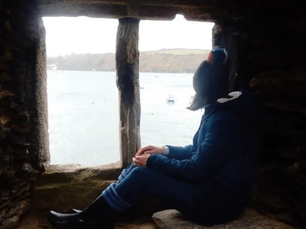 Penny Bedford sitting in a window of Polruan Blockhouse looking out to sea