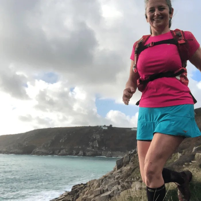 Woman running on the coast path from Lamorna Cove