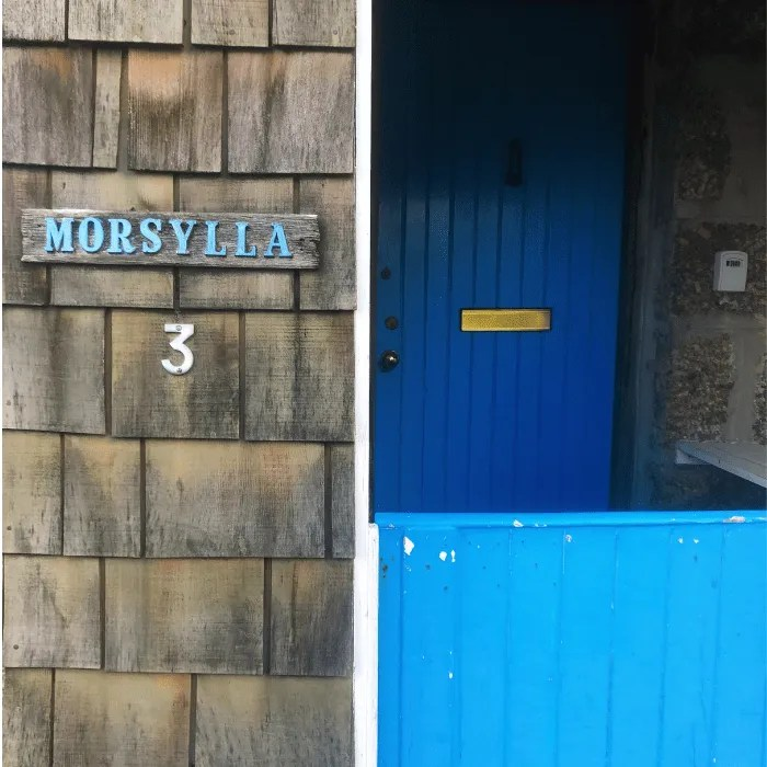 A house with a blue stable door and Morsylla name plaque