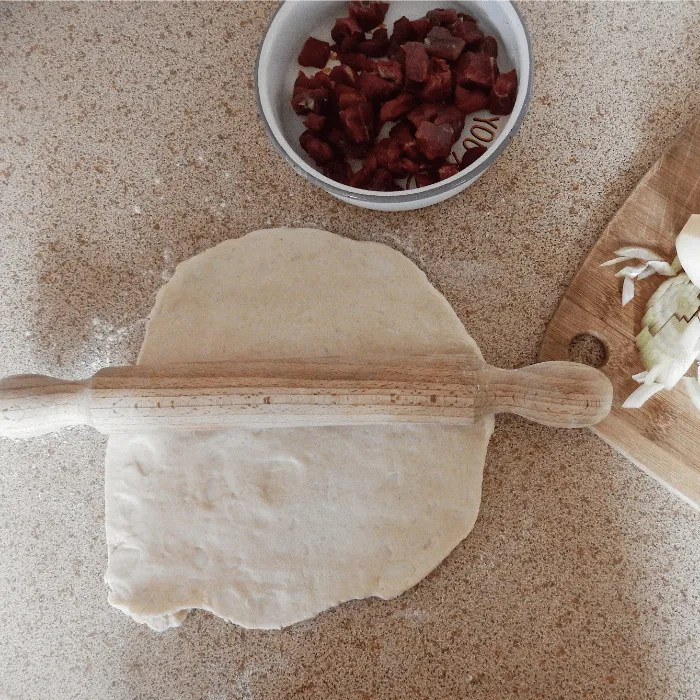 partly rolled pastry with a rolling pin and a dish of beef