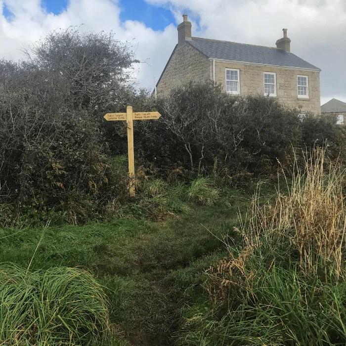 A house with a coast path sign