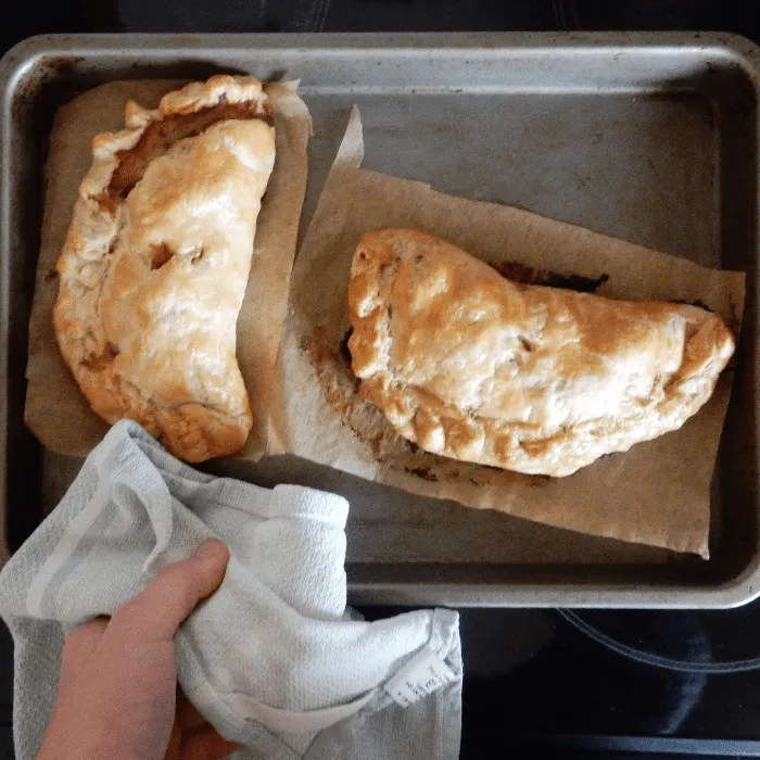 Two Cornish Pasties being taken out of the over