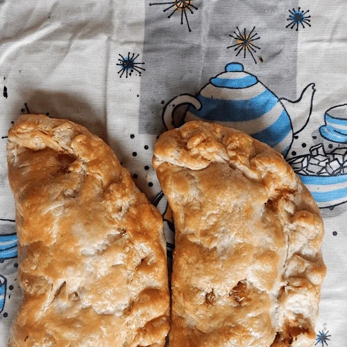 Two cooked Cornish Pasties on a beeswax wrap