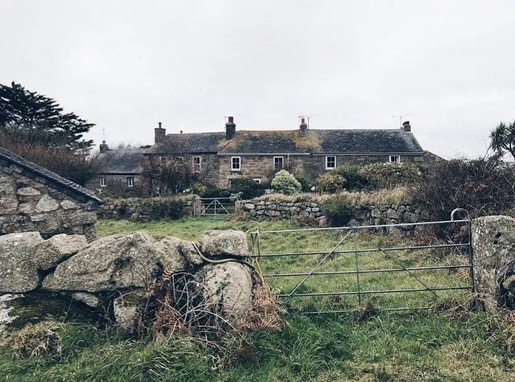 A cottage with fields and a stone wall