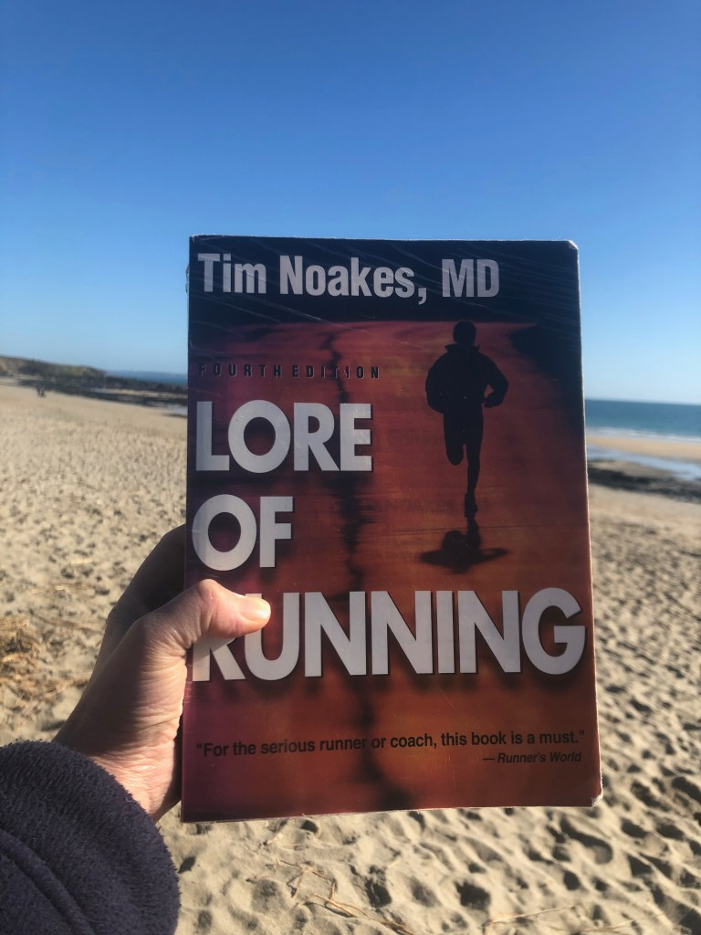 Lore of Running book being held up on a beach