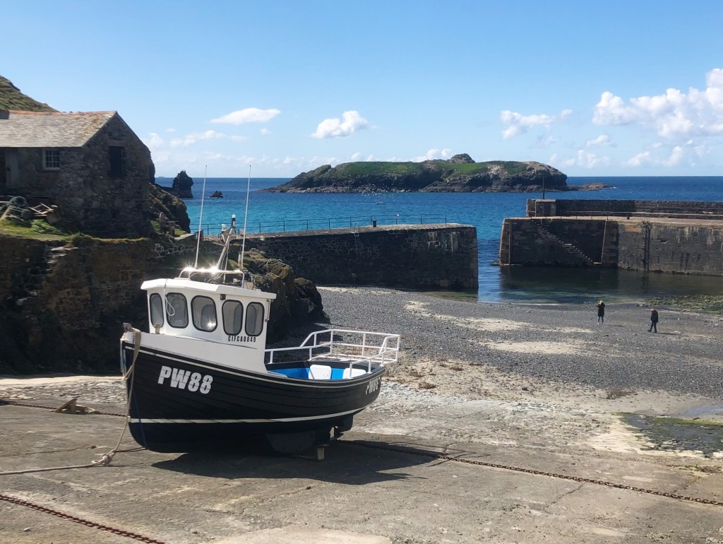 Mullion Cove at low tide with a fishing boat on the shore