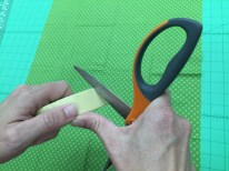 Use paper scissors to cut a slit several layers deep into the masking tape.