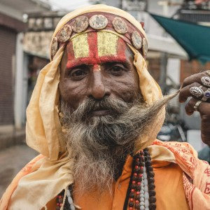 A Baba adorned in ritual face paint, twirls his long moustache. His hands and neck are bedazzled with locally crafted jewellery.