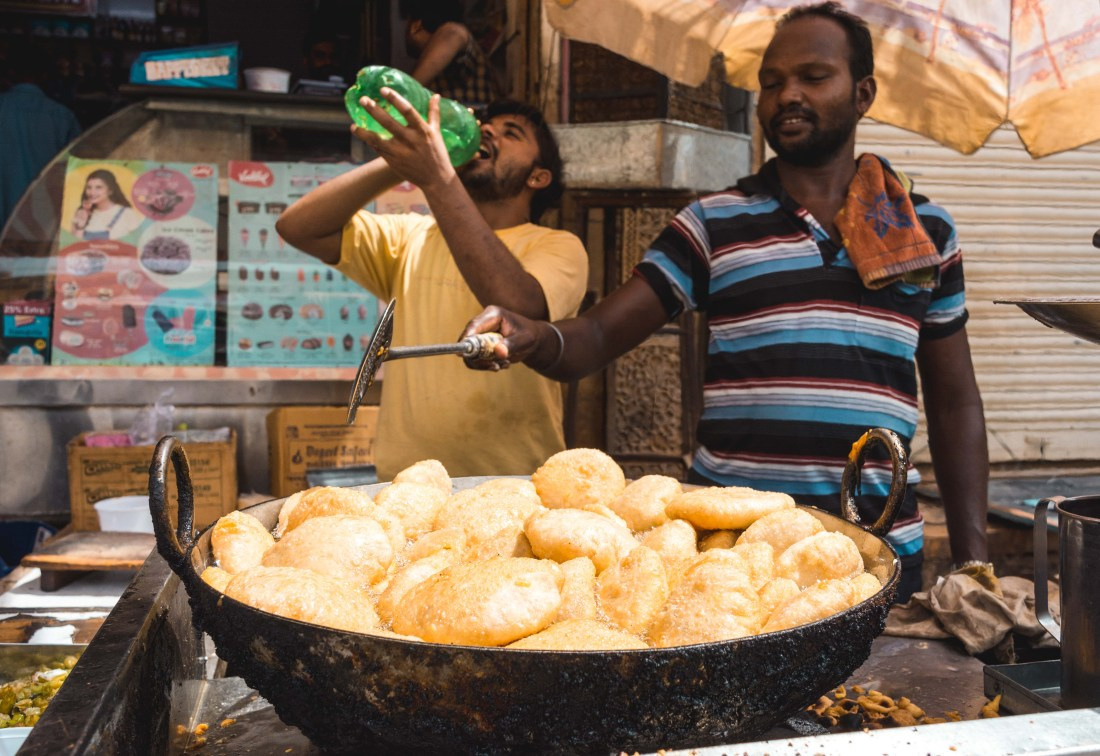 In a popular street market of Jaisalmer, two Indians prepare a fresh pot of Kachori in boiling oil. Their pan has a thick buildup of charcoal from years of use.