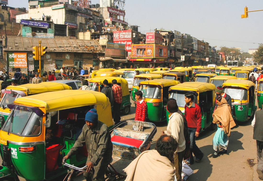 A traffic jam in India. Likely during rush hour, nothing but Tuk-tuks are visible on the rundown freeway