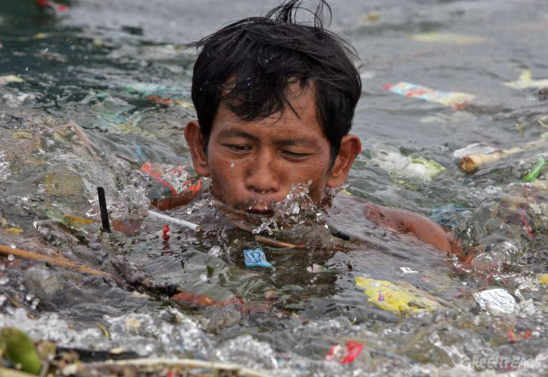 Local boatman swims amongst plastic trash discarded in Manila Bay, Philippines